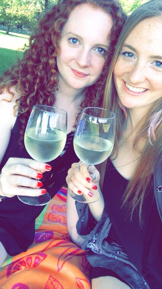 Two women sitting outside with a glass of white wine