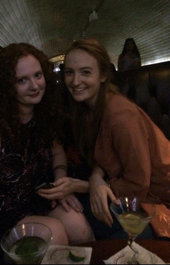 Two women sitting in a dark bar and laughing