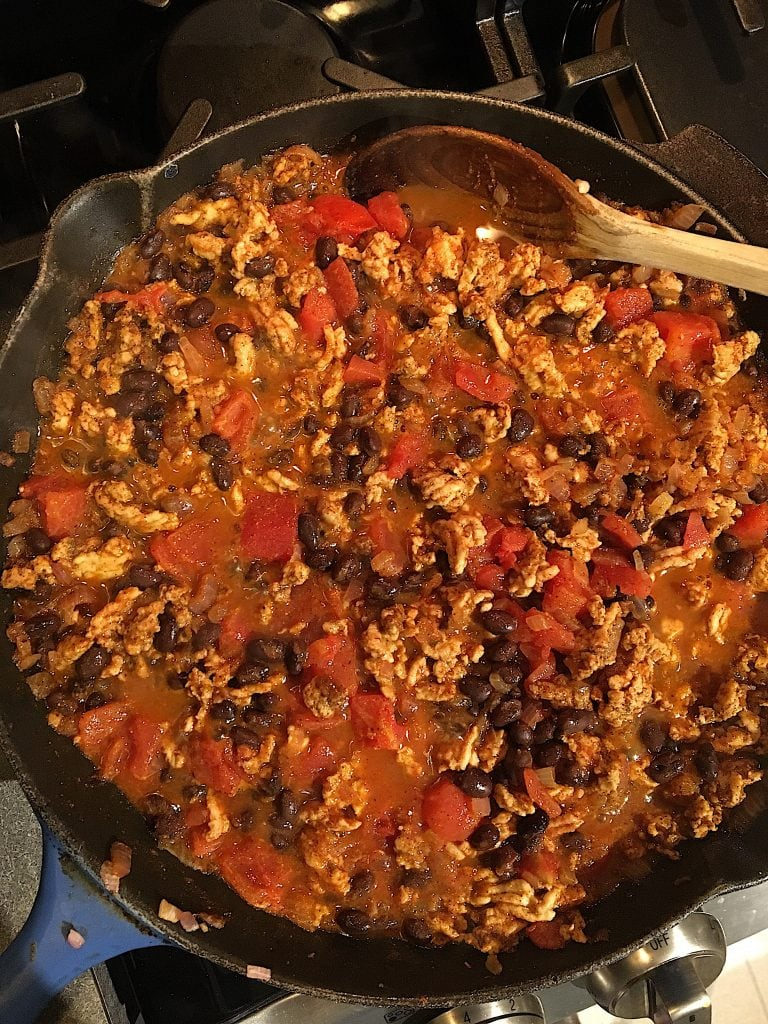 turkey and black bean enchilada filling with onion and tomato in a skillet with a wooden spoon