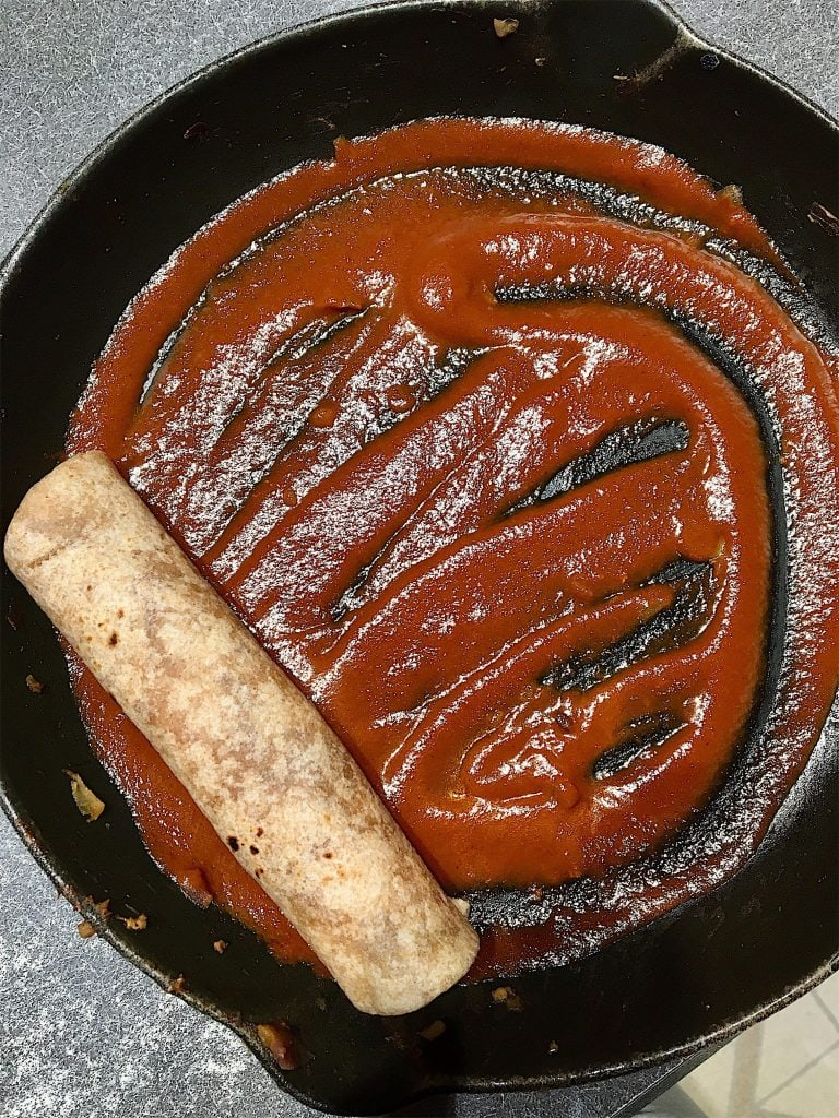 a single rolled tortilla in a skillet with enchilada sauce