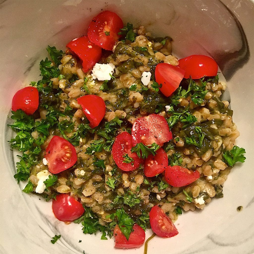 Spinach and feta farro risotto with chopped cherry tomatoes in a white bowl