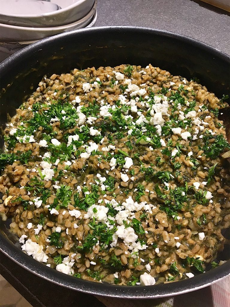 Spinach and feta risotto in a large skillet topped with parsley