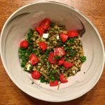 Spinach and feta farro risotto with chopped cherry tomatoes in a white bowl on a brown table