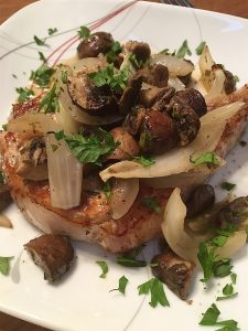 Pork chop on a white plate topped with roasted mushroom and onions, sprinkled with parsley