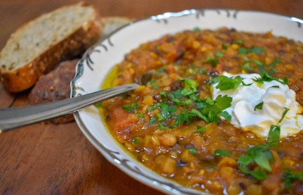 Red lentil soup in a white bowl topped with yogurt and parsley
