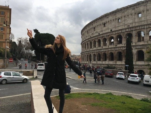 A woman standing in front of the Colosseum, jokingly saluting upwards
