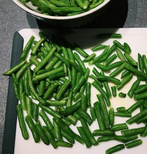 Green beans chopped up on a cutting board next to a bowl of un-chopped green beans