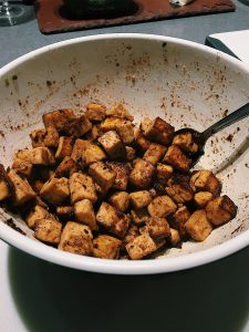 Cooked, golden brown tofu cut into 1/2 inch size chunks in a bowl with a silver spoon