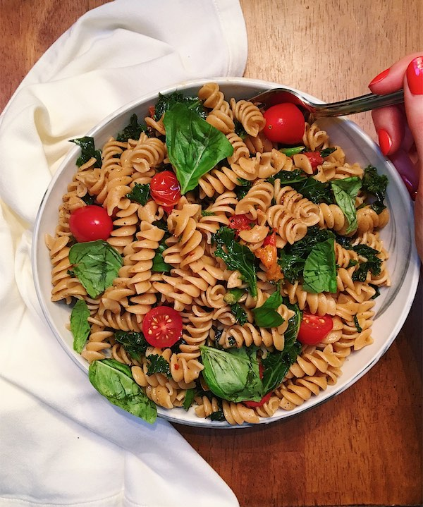 Bowl of rotini with tomato, basil, and sautéed kale