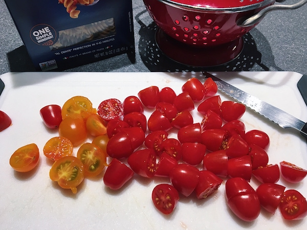 An array of cherry tomatoes on a white cutting board, cut in half
