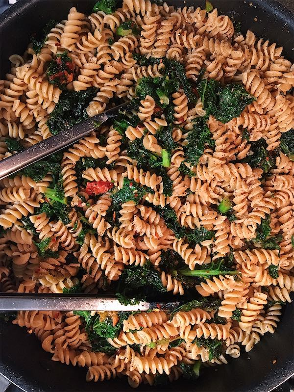 A skillet with rotini, sautéed kale, and tomatoes all tossed together