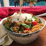 Tomato basil rotini in a bowl with vegan pasta sauce getting poured over it