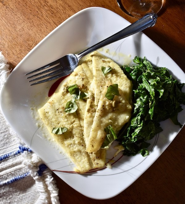 Cooked white fish on a plate topped with lemon-caper sauce served with sautéed kale on the side.