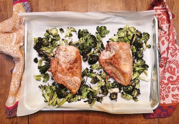 Two roasted chicken breasts on a sheet pan with broccoli and scallions
