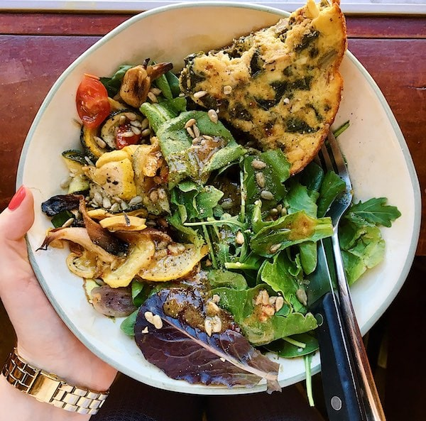 Green salad with leftover roasted vegetables and a piece of frittata in a bowl.