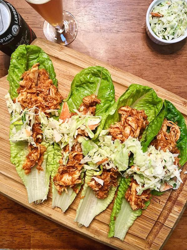 Shredded bbq chicken in 4 lettuce cups, each one topped with coleslaw.