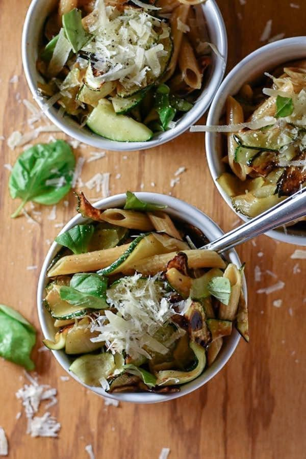 Overhead view of 3 small bowls of penne pasta with zucchini, parmesan, and basil.