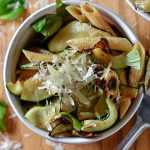 Overhead shot of a white bowl of penne pasta with zucchini, basil and parmesan.