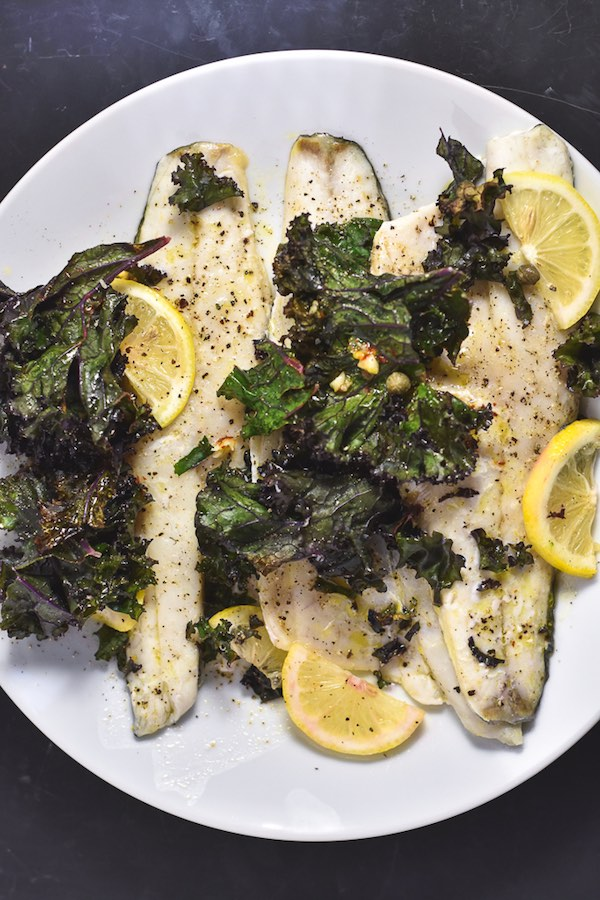 A white plate with 3 filets of roasted white fish, roasted kale, and lemon slices on it.