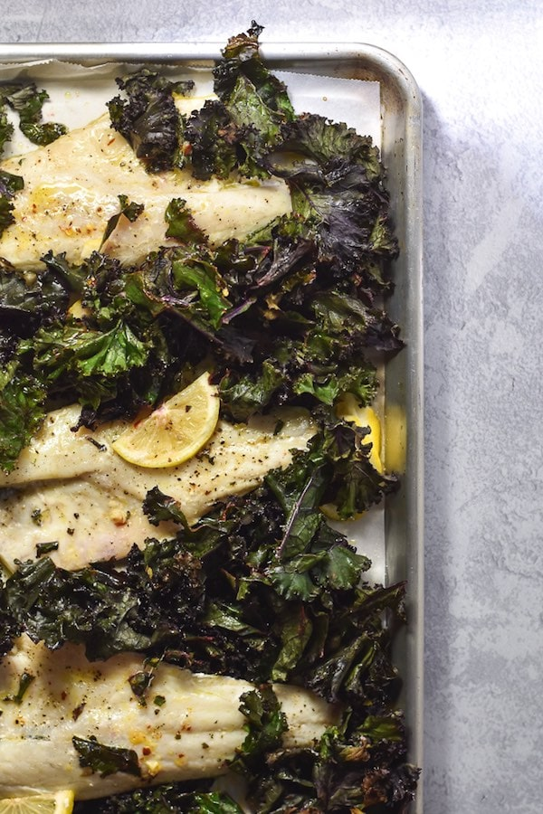 An upper right-hand view of a sheet pan with roasted white fish, kale, and lemon slices on it.