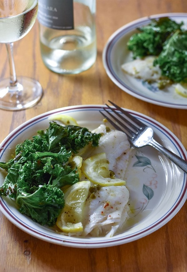 A plate with a piece of roasted fish, lemon slices and green kale. There is a glass of white wine in the background.