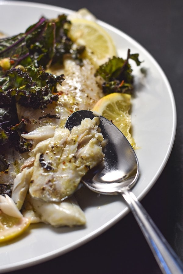 Up-close side view of a piece of roasted white fish getting cut into with a silver spoon on a white plate with kale and lemon slices.