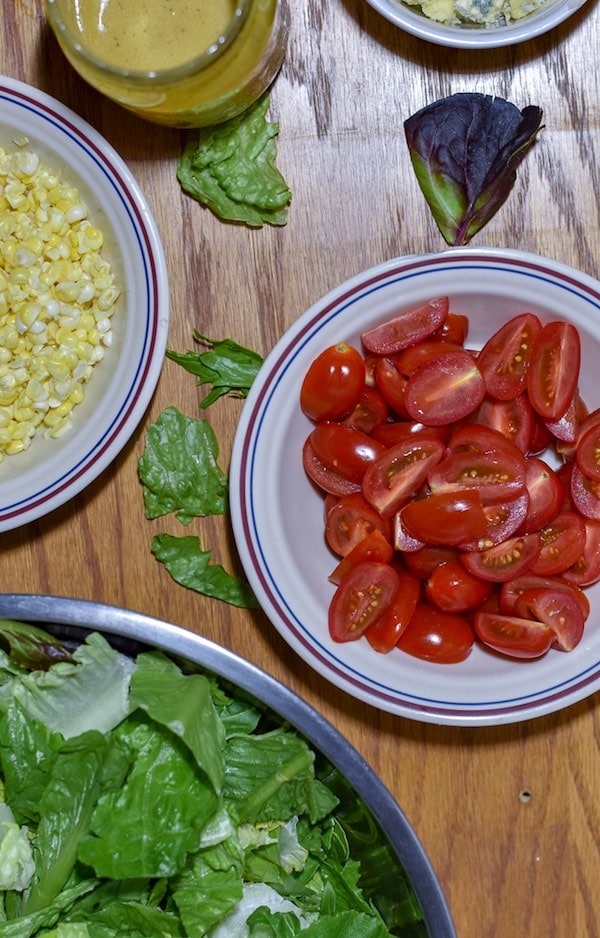 3 bowls: one with corn kernels, one with chopped cherry tomatoes, one with lettuce