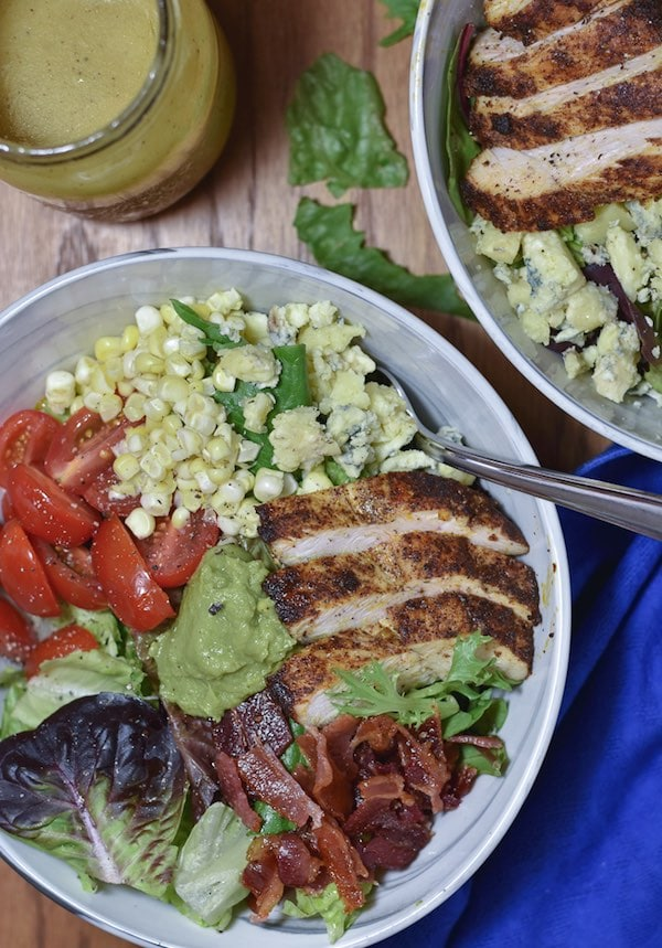 Two bowls of Cobb salad with a fork in one.