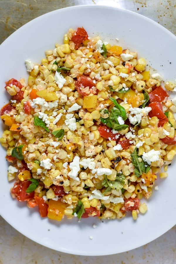 Grilled and Raw Corn Salad on a white plate- a mix of fresh and charred corn with cherry tomatoes, mint, and feta.