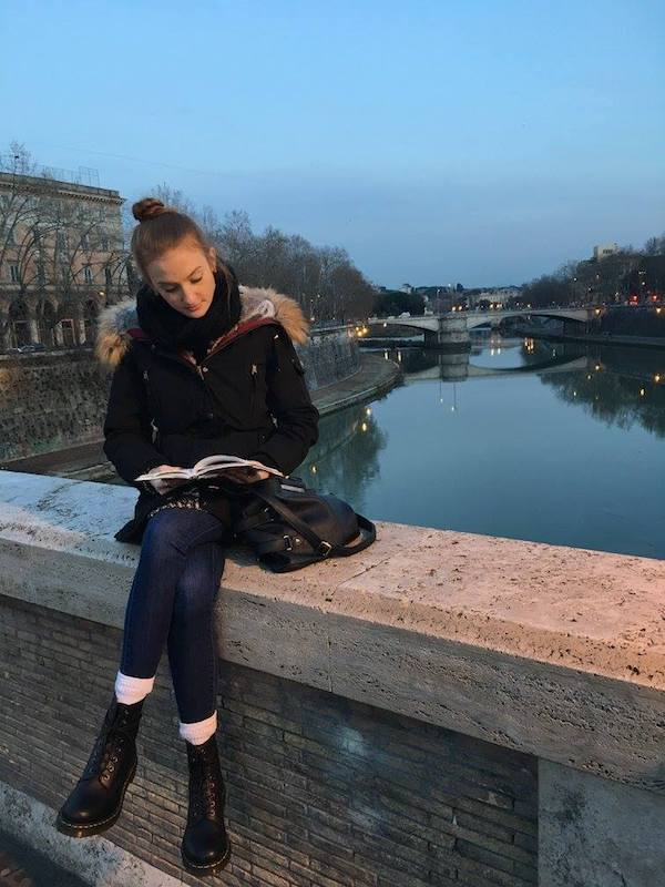 A woman sitting on a ledge on a bridge over a river, reading a book
