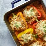 4 cooked, stuffed peppers in a roasting pan.