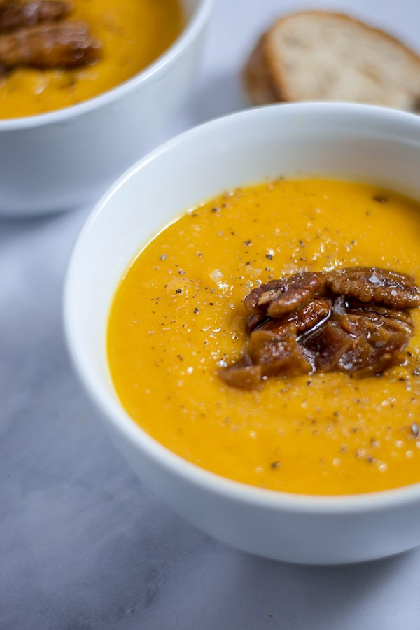 Up-close and side view of a bowl of butternut squash soup in a white bowl, topped with pecans and chopped apricots.