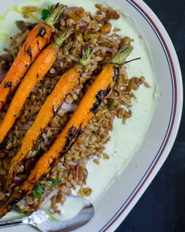Overhead shot of a plate of whole roasted carrots on top of a farro salad.
