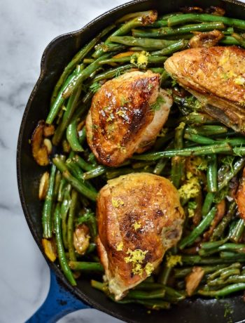 Overhead shot of cooked green beans and chicken breast in a blue cast-iron skillet.