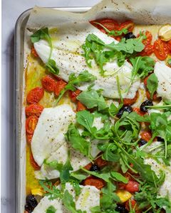 Overhead shot of flounder with tomatoes, olives, and arugula on a sheet pan.
