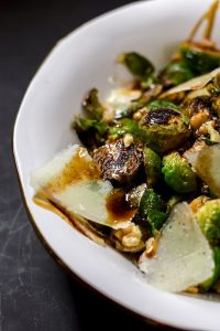 Cooked Brussels sprouts in a white bowl with walnuts, parmesan, and pomegranate molasses.