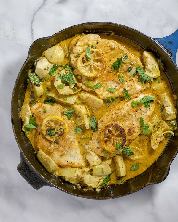 Chicken with lemon and artichokes in a blue skillet.