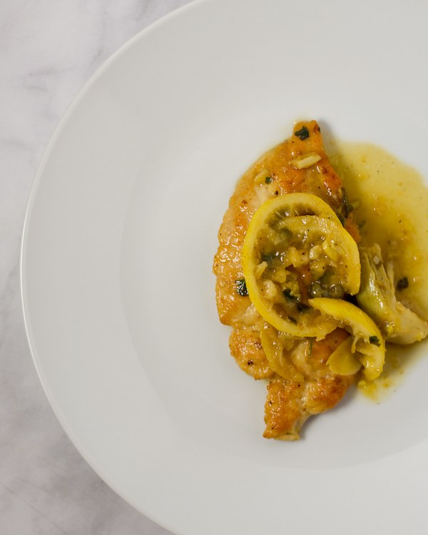 Chicken with lemon and artichokes on a white plate.