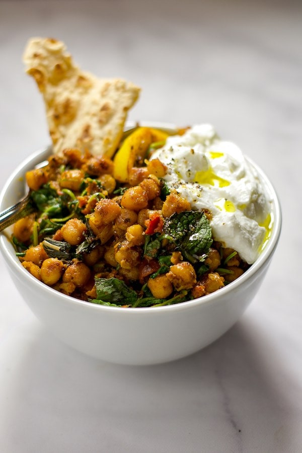 Chickpeas, sun-dried tomatoes, olives, and lemon in a white bowl, topped with yogurt and a slice of pita.