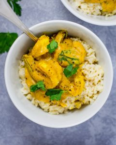 Seared shrimp in a yellow curry sauce over brown rice in a white bowl.