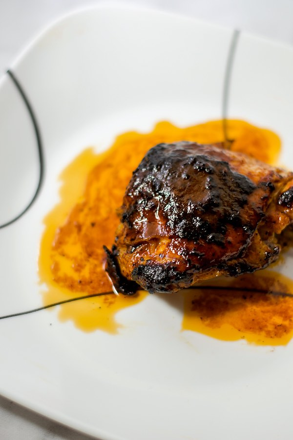 Roasted chicken thigh on a white plate covered in hot sauce.