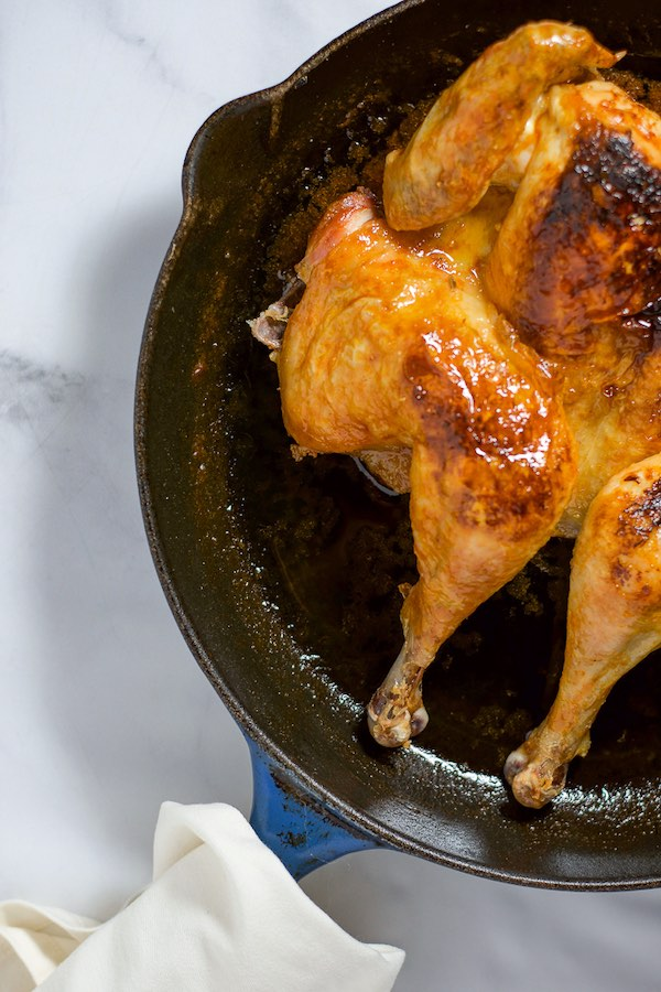 Overhead shot of a roast chicken on a skillet with hot sauce.