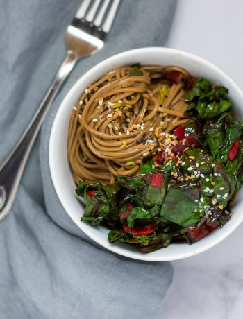 Overhead shot of a white bowl of soba noodles with sautéed swiss chard.