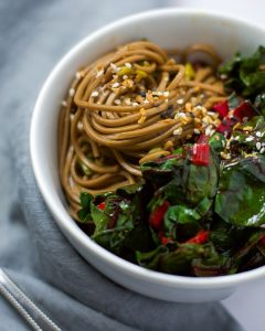 Up-close side view of a white bowl of soba noodles with sautéed swiss chard.