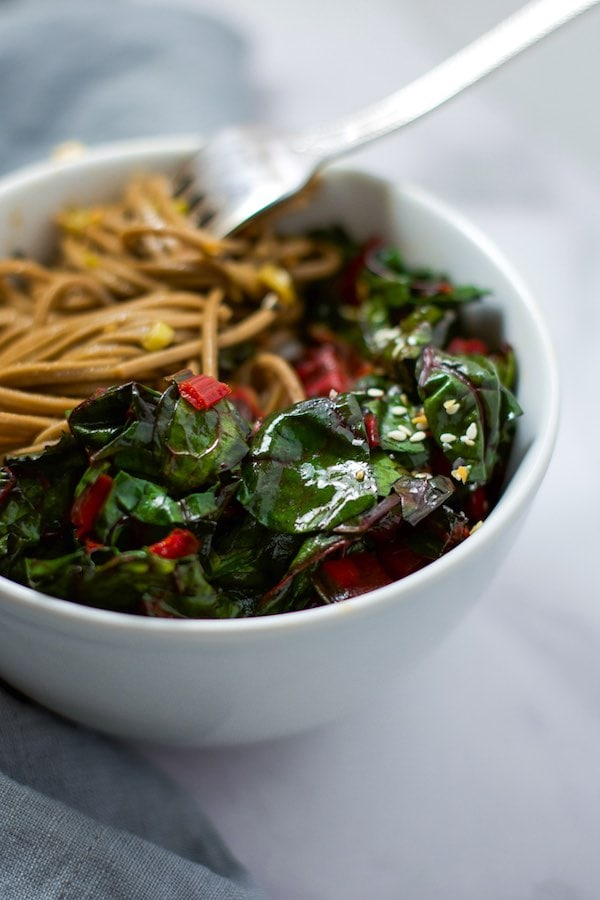 Up close side view of a white bowl with sautéed swiss chard and soba noodles.