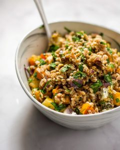Farro salad with roasted vegetables in a white bowl with a silver fork.