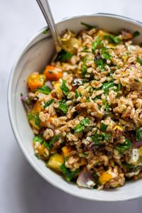 Overhead shot of a farro salad with roasted vegetables in a white bowl.