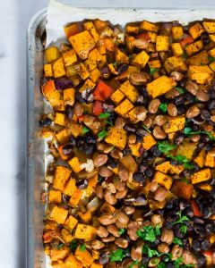 Overhead shot of a sheet pan with burrito filling: sweet potatoes, peppers, onions, and beans.