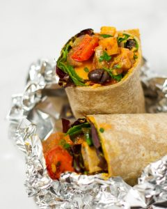 Side view of a burrito cut in half, filled with sweet potatoes peppers, onions, greens, and queso.