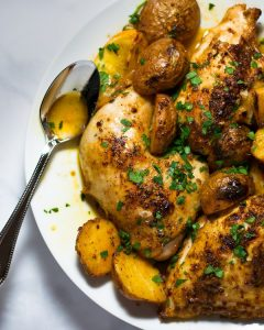 Overhead view of roasted paprika chicken and potatoes garnished with parsley on a white plate with a silver spoon.